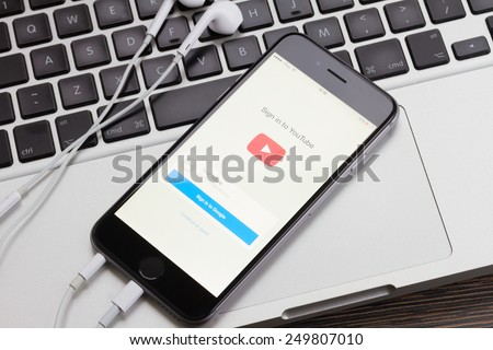 WARSZAWA, POLAND - DECEMBER 16, 2014. New Apple Iphone 6 in gray space black color with YouTube screen on Macbook keyboard.  - stock photo