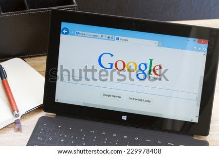 WARSZAWA, POLAND - OCTOBER 10, 2014. Google search page on screen of Windows tablet Surface.  In December 2013 Alexa listed google.com as the most visited website in the world. - stock photo