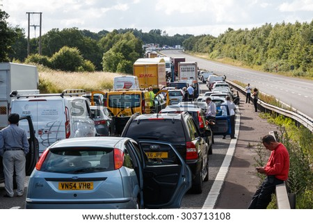Warwickshire,UK - June 28th 2015:Drivers standing next to lines of queing traffic in a motorway traffic jam after an accident.  This happened on the M40 in England. - stock photo