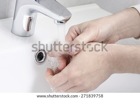 wash basin and running water from the tap in chrome bathroom - stock photo