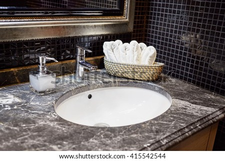 Wash bowl, mixing taps and basket with fresh towels in bathroom. - stock photo