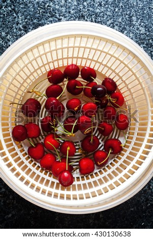 Wash fresh ripe Cherry Fruit in Salad spinner. on a black marble table - stock photo