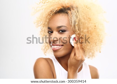 Wash makeup. Young woman washing her face with a cotton swab cosmetics - stock photo