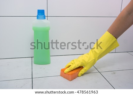 Wash the tile in the bathroom. Female hand in a yellow rubber glove with sponge. Wiping the floor. Green liquid cleanser in the bottle.