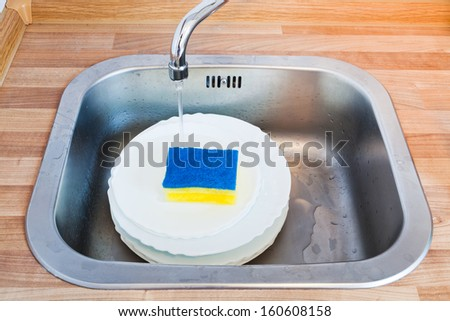 wash-up by cleaning sponge in metal washbasin in kitchen - stock photo