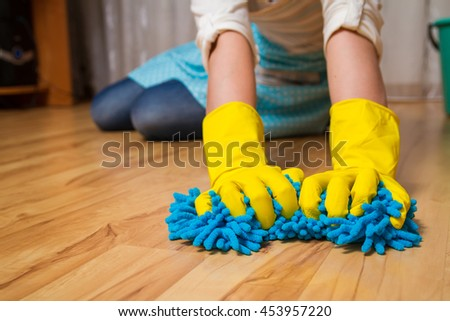Wash wood floor concept. Young woman wipes the floor with a cloth gloves, sitting on his lap - stock photo