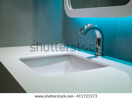 Washbasin faucet white light blue ceramic wall.