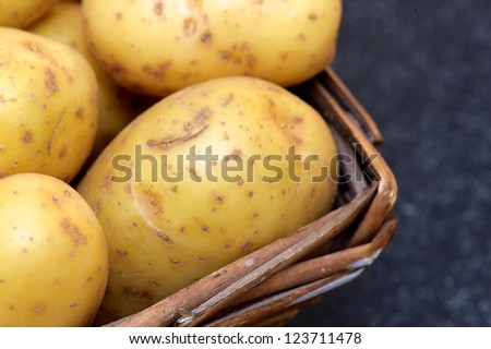 Washed organic baking potato's in a farm house wooden basket - stock photo
