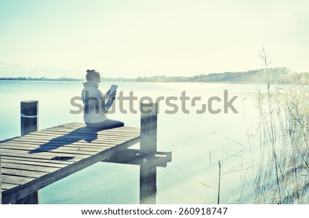 Washed out photo look. Girl reading from a tablet on the wooden jetty against a lake. Switzerland