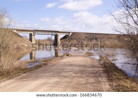 washed out road in spring flood - stock photo