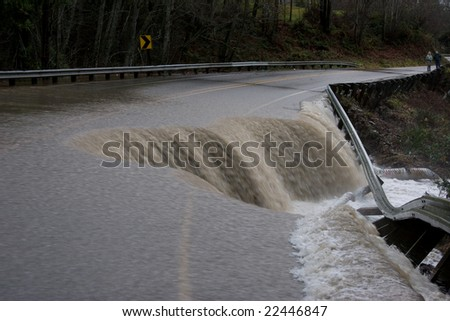 Washed out Road with Water Flowing - stock photo
