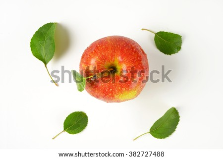 washed red apple with leaves on white background - stock photo