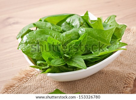 washed spinach leaves in a bowl on a wooden table