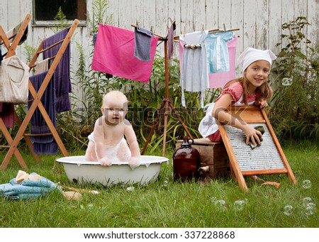Washing.  2 adorable girls - one washing clothes on a vintage scrub board and the other playing in a wash basin.