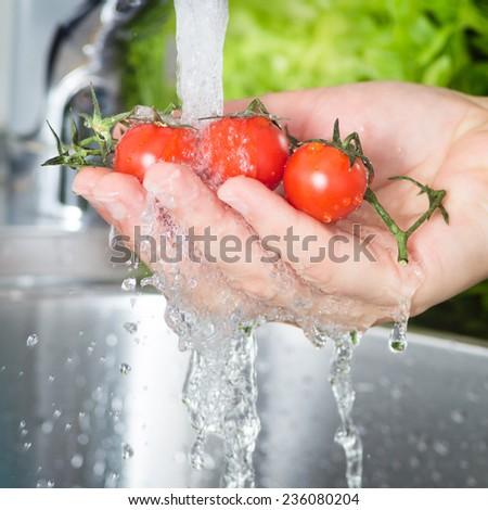 Washing Cherry Tomatoes under Running Water - stock photo