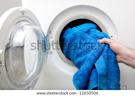 Washing clothes in a front loading washer - stock photo