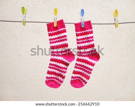 Washing day, Pink socks drying on a string - stock photo