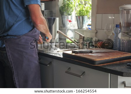 washing dishes in the kitchen with sunlight on water - stock photo
