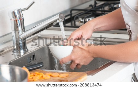 washing dishes. woman washing dishes under a running tap - stock photo