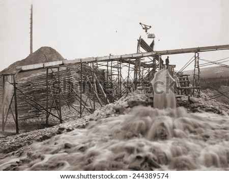 Washing gold in a sluice box placed in the stream to channel water flow. Fairbanks, Alaska, between 1910-20. - stock photo
