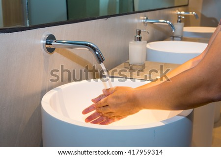 Washing hand under flowing tap water, In the bathroom at the hotel - stock photo