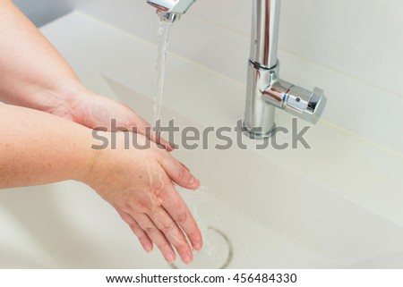 washing hand under running water