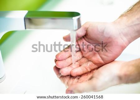 Washing hand under tap water - stock photo