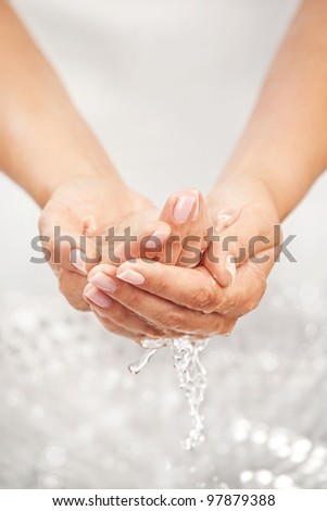 Washing hands above the sink with splashing and drops - stock photo