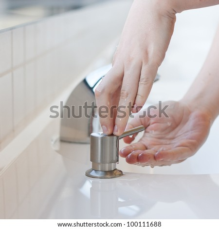 Washing hands in a public restroom - applying soap (selective focus) - stock photo