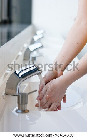 Washing hands in a public restroom (selective focus)