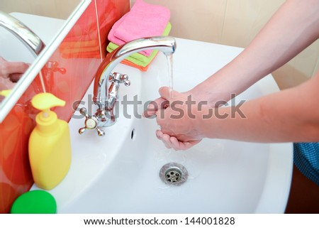washing hands in bathroom.Wash basin with mixer tap and towels - stock photo