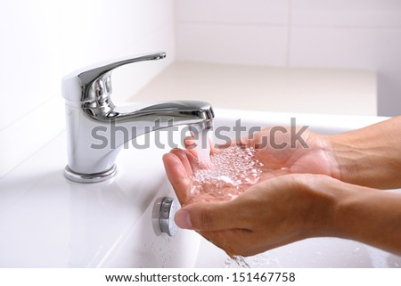 washing hands under flowing tap water in the bathroom