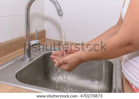 Washing Hands with streaming water in kitchen. Hygiene concept