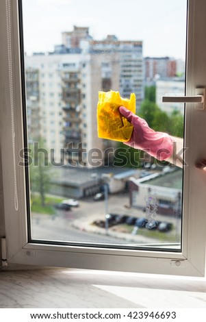 washing home window in spring - washer cleans window frame by rag in apartment house