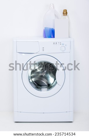 Washing machine is isolated on white background, and cleaning agents. - stock photo