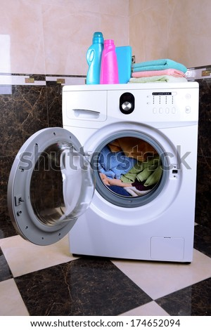 Washing machine loaded with clothes in bathroom - stock photo