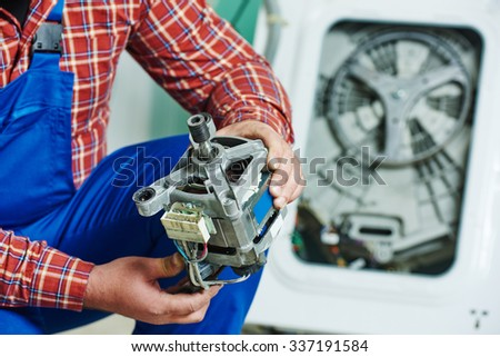 Washing machine repair. Repairer hands with electric engine motor in front of damaged unit  - stock photo