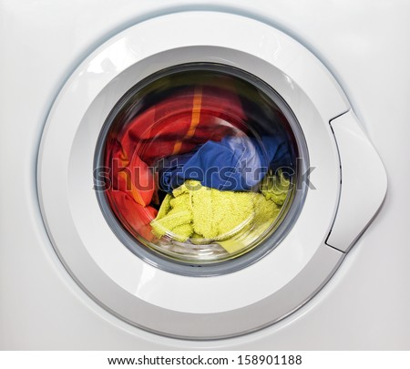 Washing machine with dirty clothes inside - stock photo