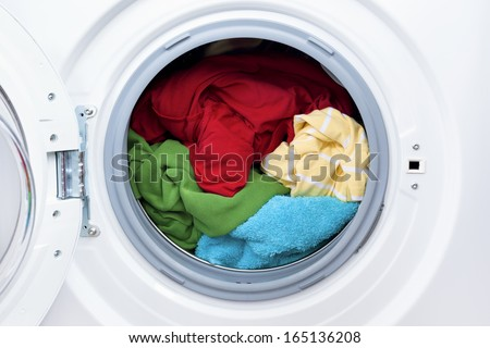 Washing machine with dirty clothes inside, studio shot