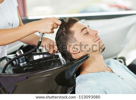 Washing man client hair in beauty parlour hairdressing salon - stock photo