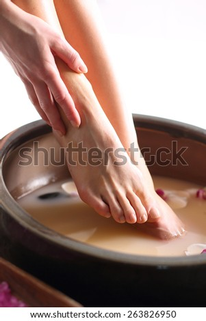 Washing of feet.A woman washes the feet in a bowl of water and salt to the foot - stock photo