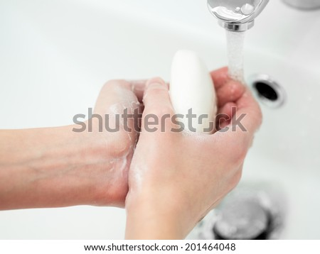 Washing of female hands with soap in bathroom - stock photo