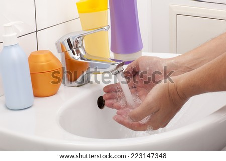 Washing of hands with soap in bathroom close up - stock photo