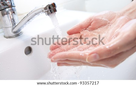 Washing of hands with soap under the crane with water - stock photo