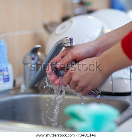 Washing of the dishes - woman hands rinsing dishes under running water in the sink