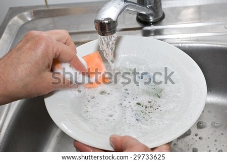Washing plate in the kitchen - stock photo