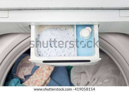 washing powder and fabric softener in washing machine,Top view - stock photo