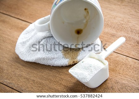 Washing powder in measuring cup with dirty fabric
