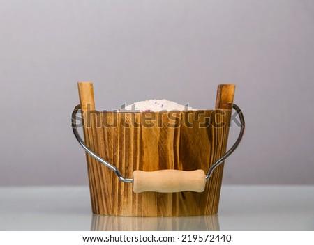 Washing powder in wooden basket on gray background - stock photo