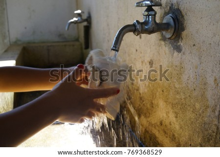 Washing The Duster With Tap Water At Outside